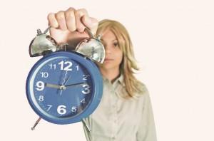 目覚まし時計を差し出す外国人女性